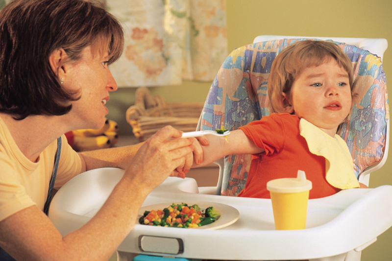 Mother having trouble feeding her daughter who is a picky eater