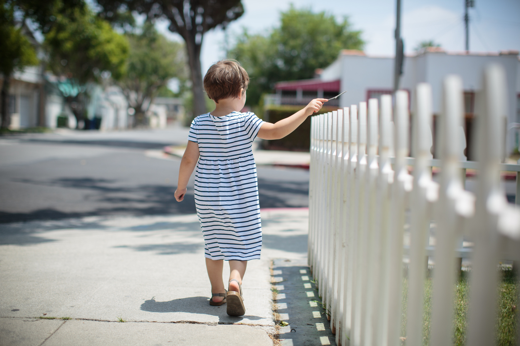 Little toddler girl in summer dress walking away along white fence. Back view.