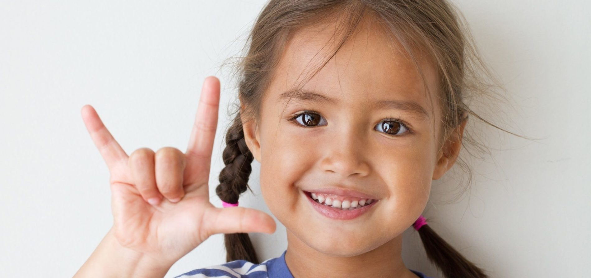 cute little girl showing I love you hand sign