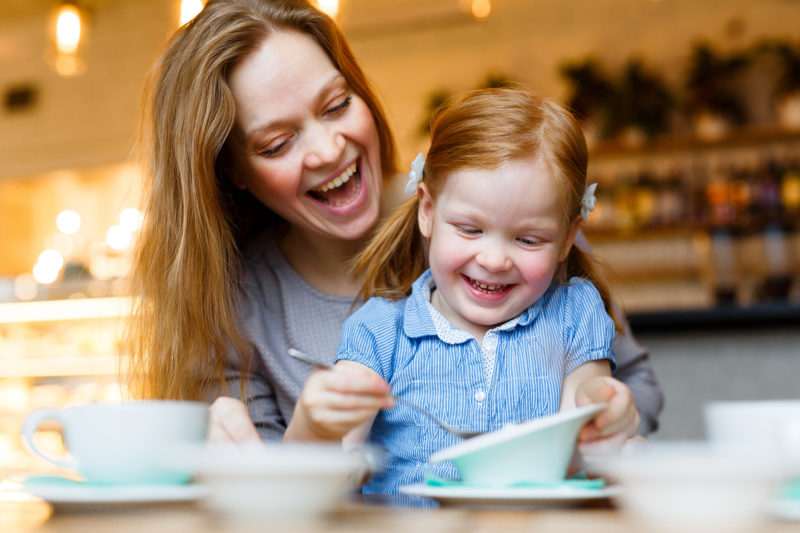 Cheerful woman and her little daughter eating in cafe
