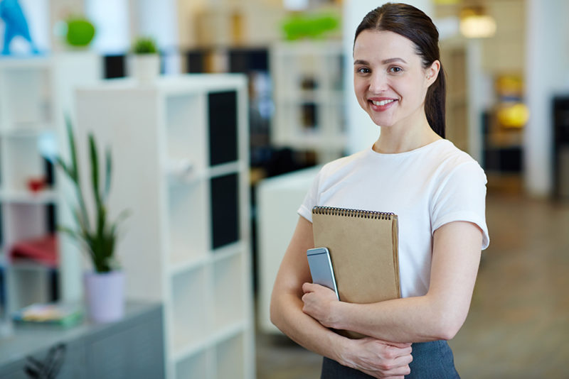 Young woman smiling happily while looking at camera standing in modern office