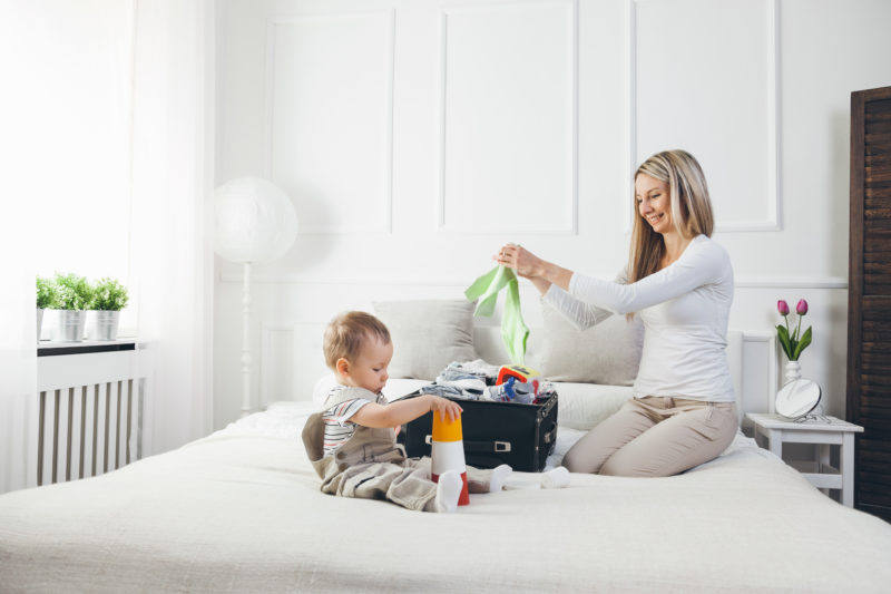 Travelling with kids. Happy mother with her child packing clothes for their holiday