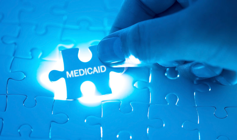 Doctor holding a jigsaw puzzle with MEDICAID word