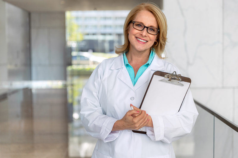 doctor physician, healthcare professional portrait, smiling sincere with clipboard at hospital clinic