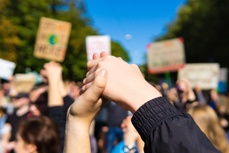 two young people at a rally, joining hands together signaling peace, unity and decisiveness in front of a crowd carrying protest placards