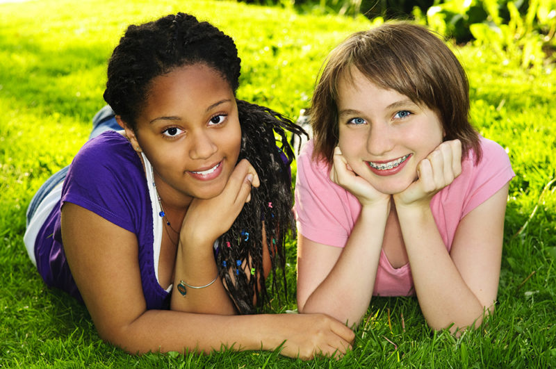 Two happy teenage girls laying on grass