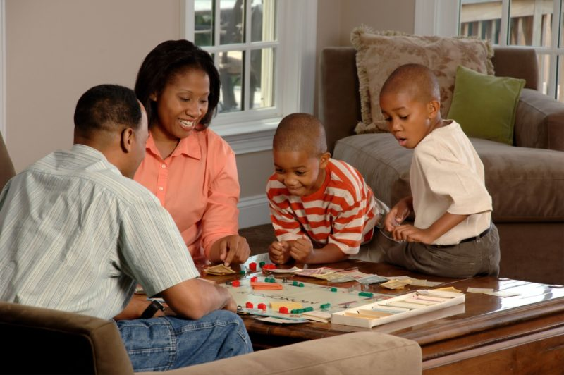 An African-American family (adult male and female and two male children) sit around a coffee table playing a board game
