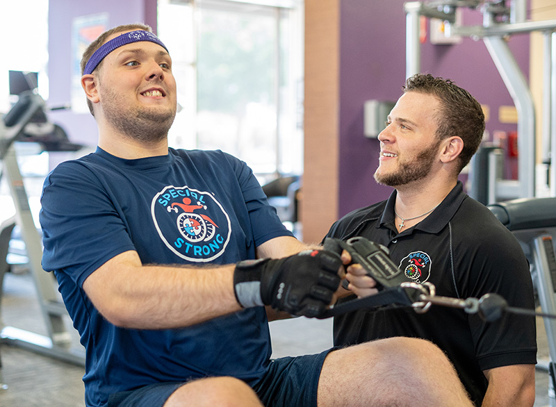 Daniel Stein, founder of Special Strong, performing a low row with scapula retraction to improve the posture of his special needs client, Robert.