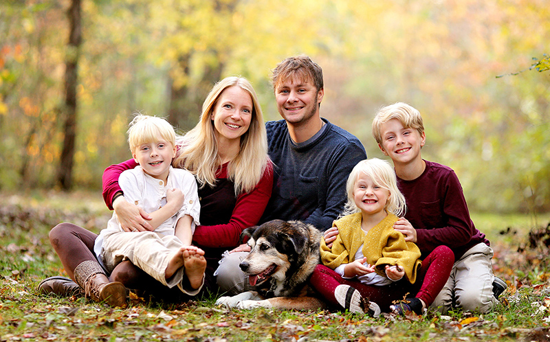 Portrait of Happy Young Family with three Cute, Smiling Children and their Pet Dog on Autumn Day