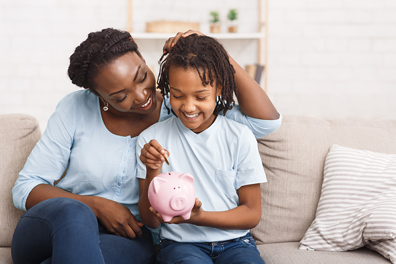 African American mother and daughter putting money in piggy bank