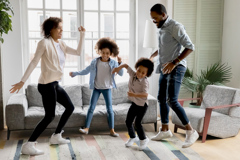 African American family dancing in living room