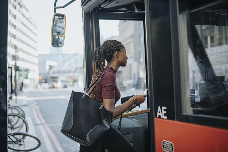 woman getting on the bus commuting to work