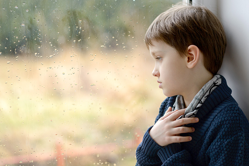 depressed and thoughtful little boy looking through the window on a rainy day
