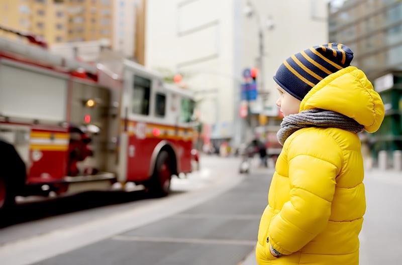 Little boy watches a fire engine