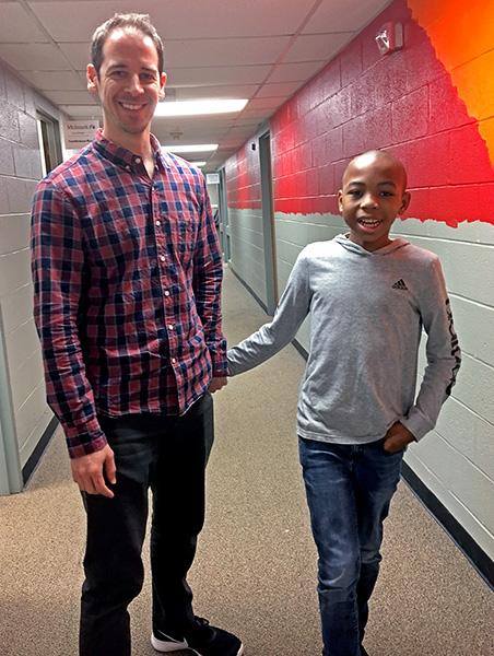 Dr. Bradley Stevenson and Simeon walk through the halls of Melmark Carolinas.