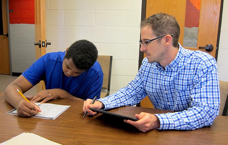 Dr. Bradley Stevenson admires the drawing skills of student Tyler.